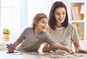 mother and daughter working on a puzzle together