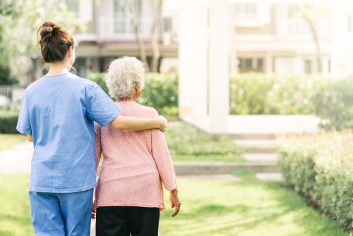 caregiver walking with elderly woman outdoors